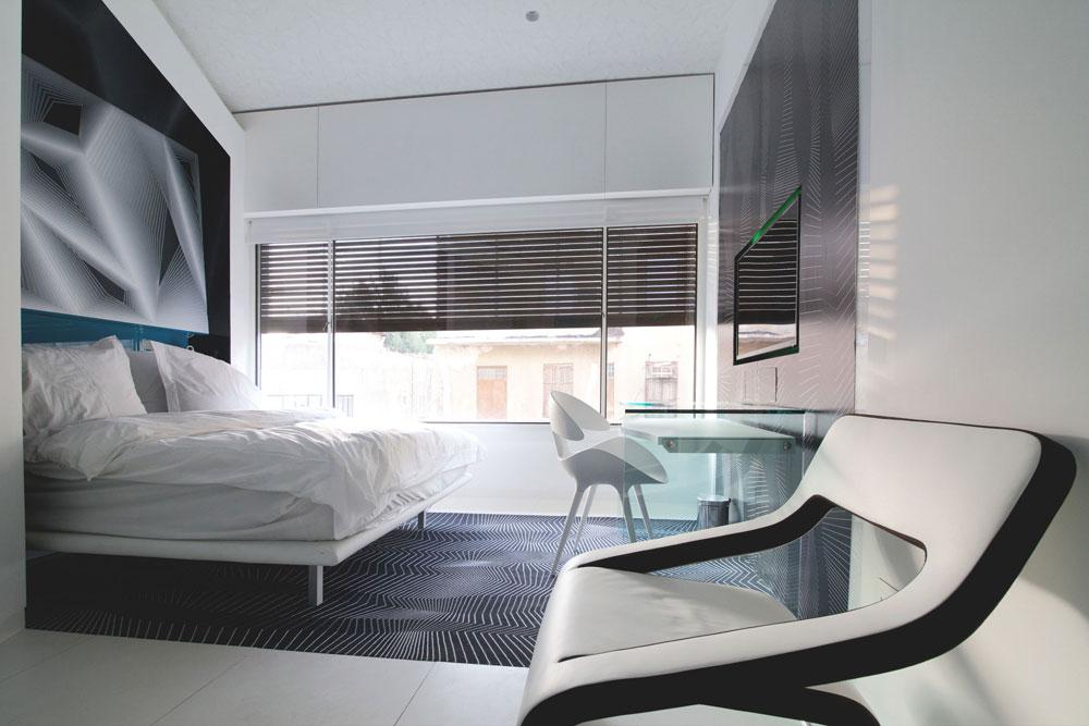 הבסיס הוא רצפה לבנה, שעליה נפרש שטיח שחור בהדפס גיאומטרי לבן. כל קירות החדר, כמו גם התקרה ודלתות הזכוכית המובילות לחדר הרחצה, חופו בהדפסים גיאומטרים בגווני שחור ולבן (צילום: דור נבו)
