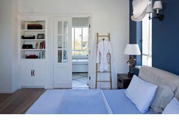 בין חדר השינה לחדר הרחצה מפרידה דלת עץ לבנה וכפולה, שבה שובצו חלונות זכוכית (צילום: שי אפשטיין)