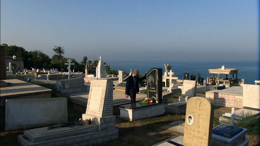 בסדרה: ניקולה קובלובה (שלום מיכאלשווילי) מקעקע את שמות משפחת אסולין על זרועו, כשהוא נשען על קבר אחיו (שנבנה לצורך הסצינה). במציאות: בית הקברות הנוצרי-אורתודוקסי, בראש רכס הכורכר המשקיף על הים בקצה יפו בצמוד למרכז פרס לשלום (צילום: רם שוויקי  )