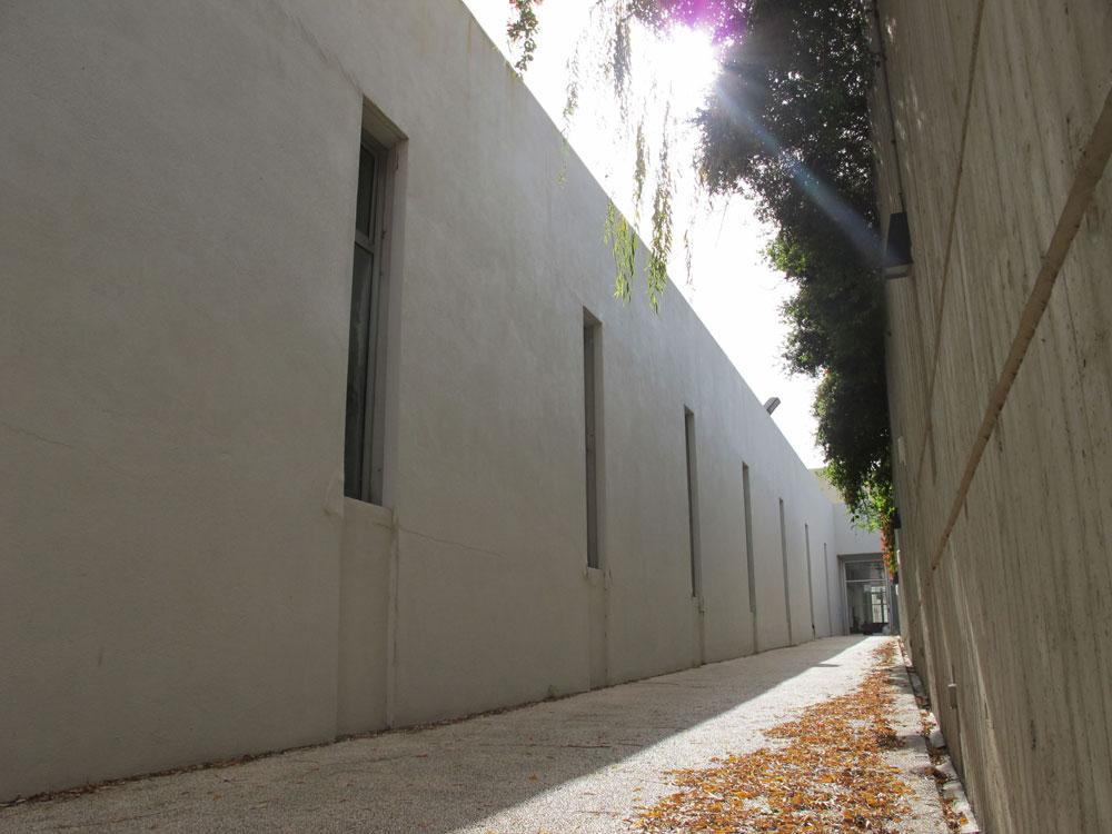 שביל הכניסה תחום משני עבריו בקירות גבוהים. ''נבחרה קומפוזיציה מופנמת, מרוכזת בעצמה ומאורגנת מסביב לחצר פנימית'', מסבירה האדריכלית (צילום: מיכאל יעקובסון)