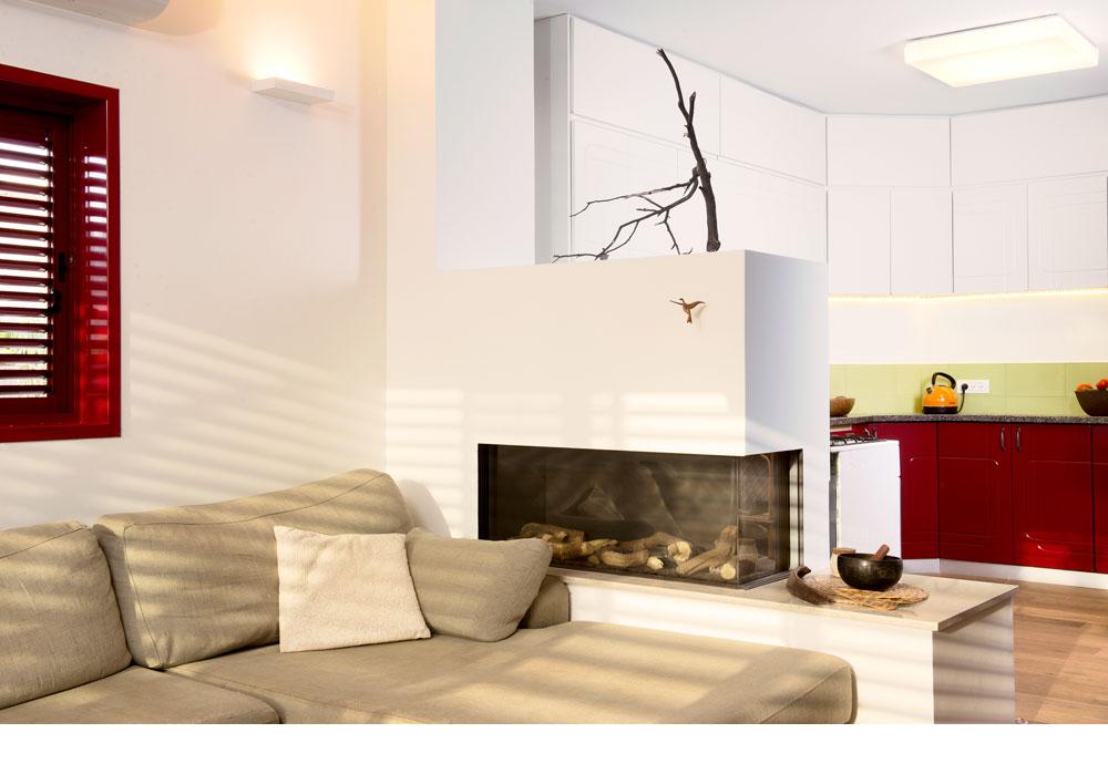 הקיר שהפריד בין הסלון למטבח הוחלף בקיר גבס נמוך, שבתוכו הותקן קמין (צילום: דורון עובד)