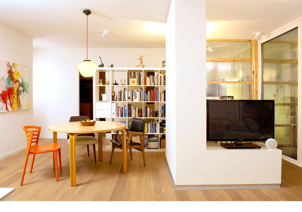 חדר העבודה (בתמונה מאחורי מסך הטלוויזיה) נתחם במסגרות עץ אורן ומחיצות מפוליגל – החלטה שבזכותה מרוויח החדר אור מהסלון (צילום: דורון עובד)