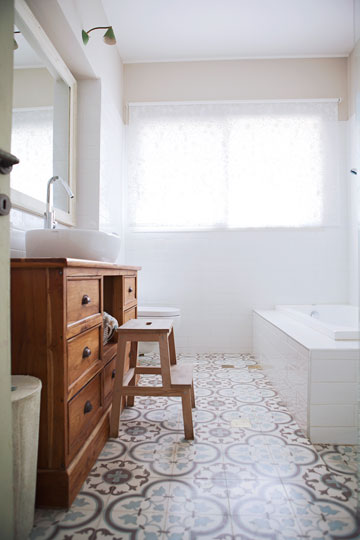 העיצוב הנקי של חדרי האמבטיה כולל מרצפות מצוירות, ארון עץ המשמש משטח לכיור ואריחי קרמיקה לבנים (צילום: ליאן מונין)