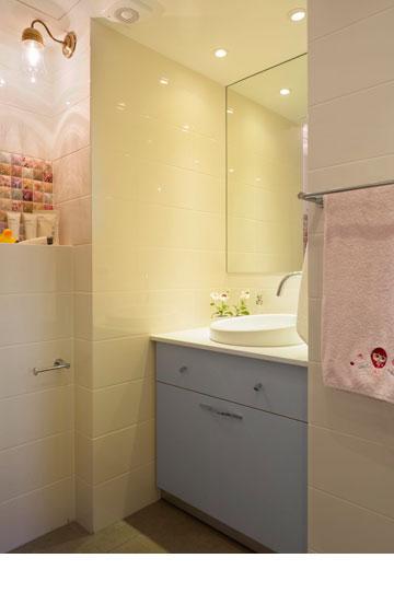 חדר הרחצה של הבנות: אריחים לבנים, שידה תכולה ואריחי פסיפס ורודים (צילום: שי אפשטיין)