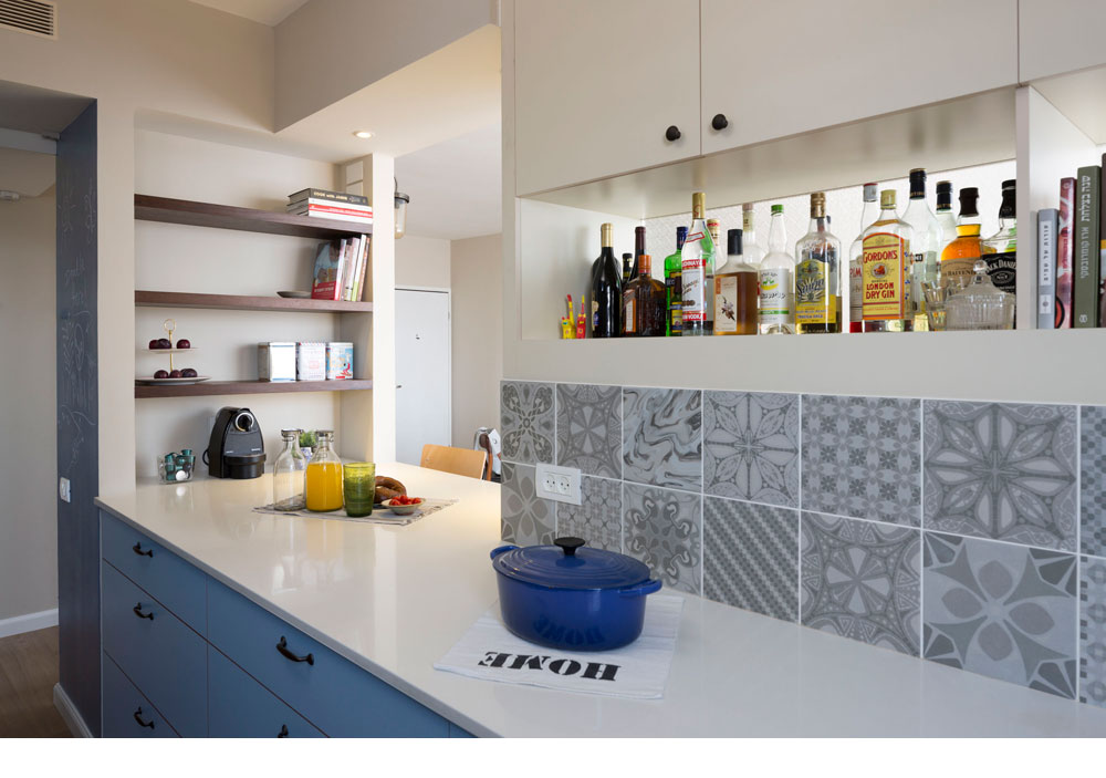 מבט מתוך המטבח לכיוון דלפק האכילה שפתוח לסלון. מדפי המשקאות סגורים מאחור ב''זכוכית סבתא'', שמאפשר לעוד אור לעבור בין הסלון למטבח (צילום: שי אפשטיין)
