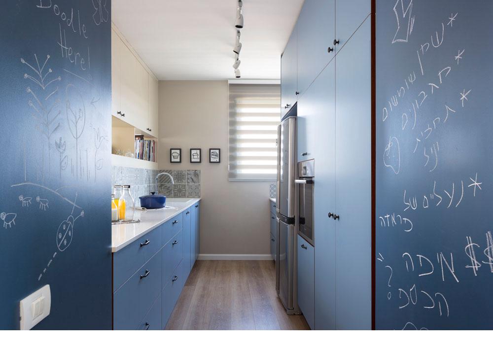 הכניסה למטבח נעשית מהמסדרון, דרך שני קירות שנצבעו בצבע לוח כחול. הארונות הכחולים נבנו בהמשך להם, בשני קווים מקבילים. מעל משטח העבודה אריחים אפרפרים עם עיטורים משתנים, ומעליהם מדפים לספרי בישול ובקבוקי משקה וארונות בצבע הקפה של הקיר, שהם חלקה האחורי של ספריית הסלון (צילום: שי אפשטיין)