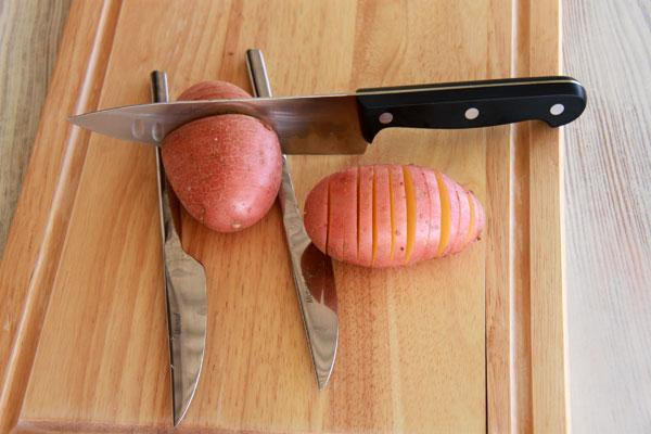 נעזרים בשתי סכינים כדי לא לחתוך את תפוחי האדמה עד הסוף (צילום: אסנת לסטר)