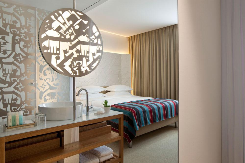 אחד מ-66 החדרים. התבנית הייחודית של האותיות העבריות מופיעה כאן כהדפס על זכוכית המקלחות וכהטבעה בראש המיטה. הרהיטים מעץ אלון ואת הצבע מוסיף כיסוי המיטה (צילום: עמית גרון)