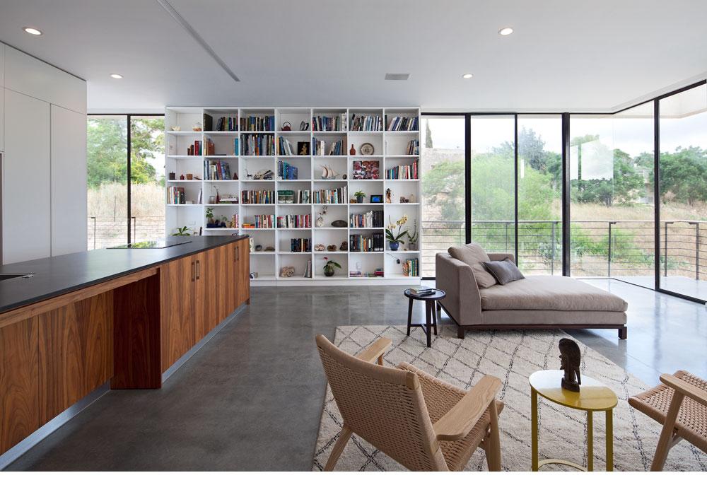ספרייה לבנה מפרידה בין שתי המרפסות בקומה. המטבח בנוי כשני קווים מקבילים: קיר ארונות גבוהים בלבן, ו''אי'' שעשוי עץ אגוז, עם משטח עבודה מאבן קיסר דמויית בזלת  (צילום: עמית גרון)