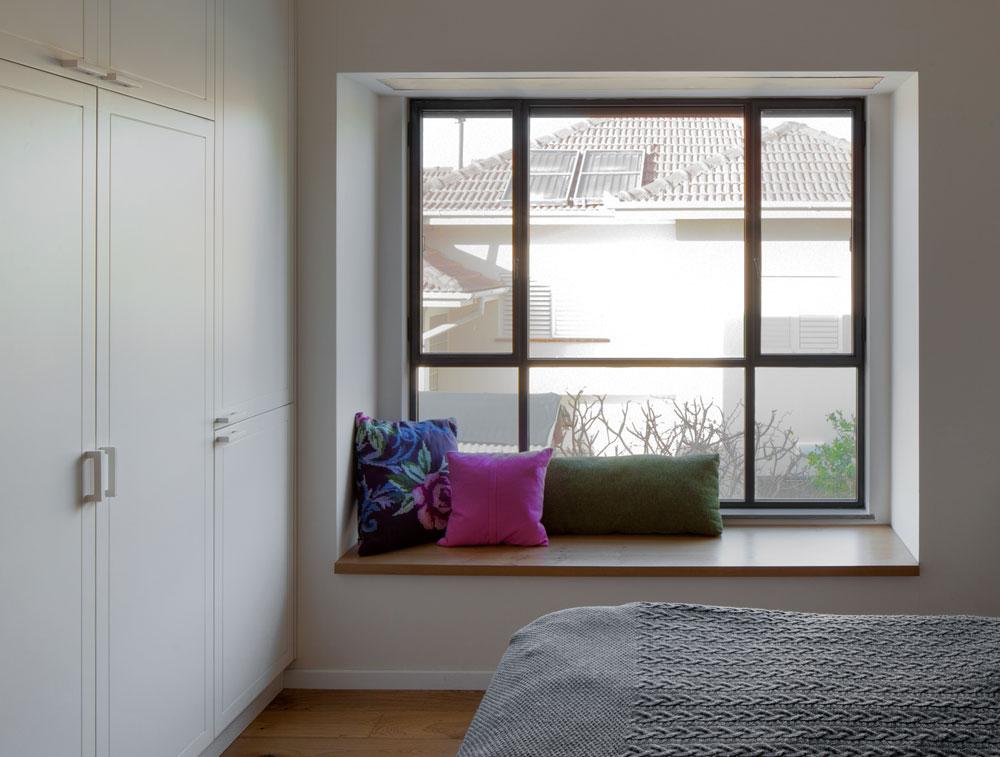 בחדר ההורים תוכנן לצד המיטה אדן חלון רחב, שעליו הונח משטח עץ אלון עם כריות נוי (צילום: אלעד שריג)