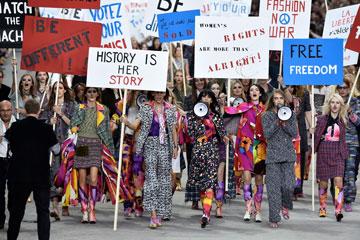 """שלטים פמיניסטיים בתצוגה של שאנל. """"אני אוהב את הרעיון של פמיניזם כמשהו קליל, בניגוד לתדמית נהג המשאית של התנועה הפמיניסטית"""", אמר קרל לגרפלד  (צילום: gettyimages)"""