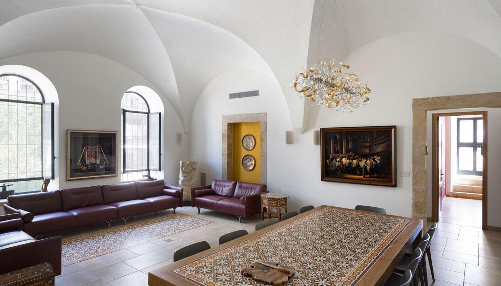 """את רצפת האבן מקשט """"שטיח"""" של אריחים מעוטרים, זהה לזה ששובץ בשולחן האוכל. על הקירות תלויות יצירות אמנות שבעל הבית אוסף, כמו צילום של מתנה שהובאה לחתונה יהודית, שנערכה בתימן לפני 100 שנה. כמו בחדרים אחרים בבית - הוחלט לשמר את משקופי האבן המקוריים, ופתחים שנחסמו הפכו לנישות דקורטיביות, שבהם מוצגים אוספים של בעל הבית (צילום: שי אפשטיין)"""
