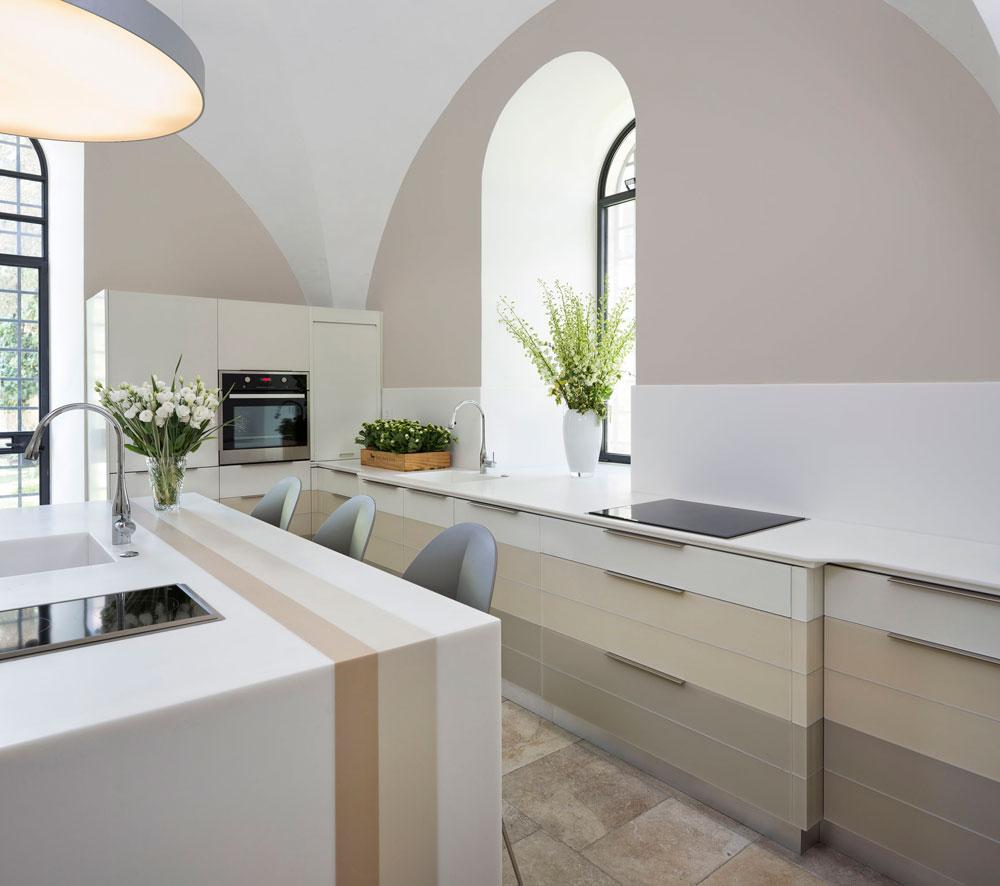המטבח עוצב בגוני לבן, חאקי ומוקה. דלתות הארונות עשויות זכוכית ומשטח העבודה והאי עשויים מקוריאן, ובהם כיורים וכיריים כפולים. גם כאן חלונות מקושתים, שחושפים קירות עבים במיוחד  (צילום: שי אפשטיין)