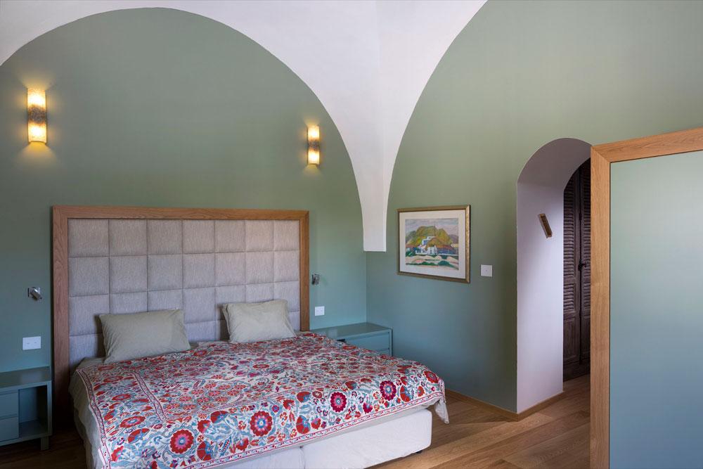 תקרה לבנה וקירות ירקרקים בחדר השינה הראשי. המיטה תוכננה במיוחד עם גב מרופד בבד שנתון במסגרת עץ, ועוצבו לה שידות צד וארון בגדים תואמים (צילום: שי אפשטיין)