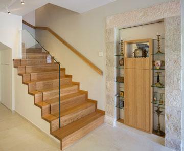 פתחים מקוריים שנחסמו הפכו לנישות. זו, למשל, משמשת להצגת חפצי יודאיקה. המדרגות מובילות לקומה עם חדרי שינה נוספים, שלא צולמו (צילום: שי אפשטיין)