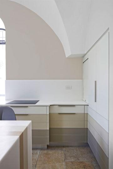 דלתות הארונות עשויות מזכוכית בגוני לבן, מוקה וחאקי - שמופיעים גם באי, שעשוי מקוריאן (צילום: שי אפשטיין)