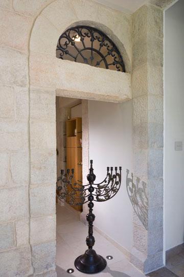 זה היה קודם דלתה של הדירה שנבנתה כתוספת לבית. הסורג העליון שופץ ומתחתיו הוצבה מנורה  (צילום: שי אפשטיין)