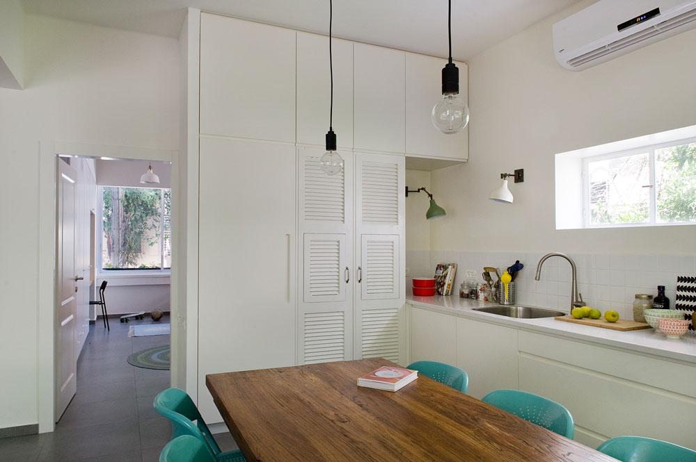 ליד ארונות המטבח הגבוהים נמצאת דלת הכניסה לחדר הילדים. כדי שיהיה מספיק מקומות אחסון תוכננו בכל חדר ארונות קיר גדולים, שנצבעו בלבן (צילום: גלית דויטש)