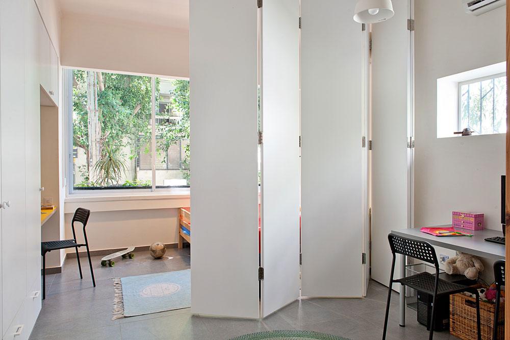 חדרם של שלושת הילדים נשאר גדול, עם אזור משחקים במרכזו. מעצבת הפנים דלית לילינטל תיכננה מחיצת אקורדיון, שמחלקת את החדר לשניים. במה שהייתה קודם מרפסת סגורה נמצאת ממלכתו של הבן הבכור, עם שולחן כתיבה ששולבה בתוך ארון הקיר. החלון הגדול עוזר לתחושה של מרחב (צילום: גלית דויטש)