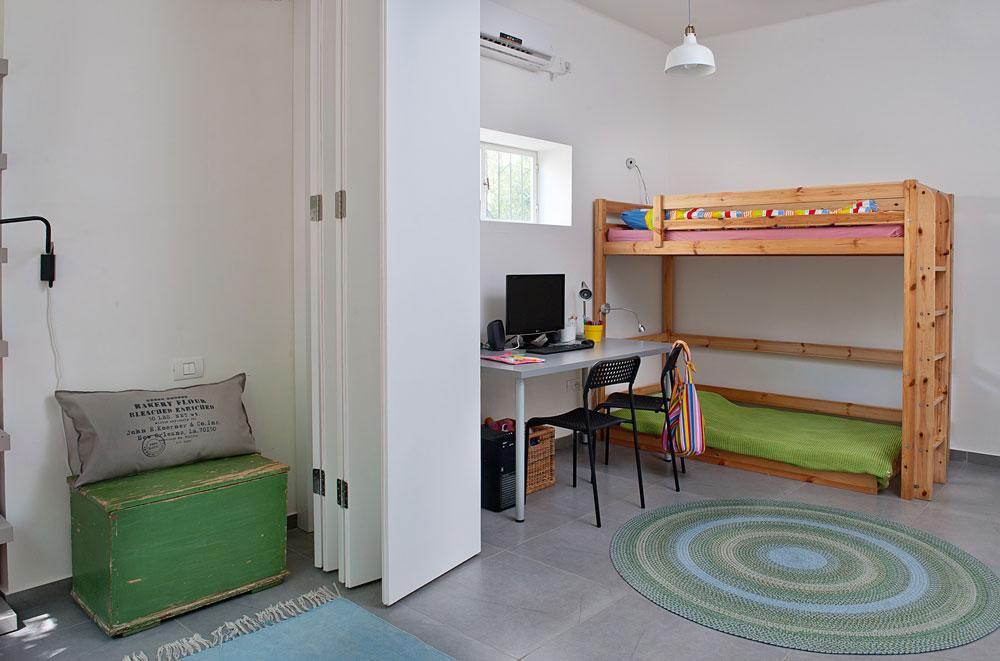 בצד השני של החדר מיטת הקומתיים של שני הילדים הקטנים יותר, וגם להם שולחן כתיבה. לפני השיפוץ ישנו השלושה באותו חדר, כשמדי לילה משכו מזרון מתחת למיטת הקומתיים (צילום: גלית דויטש)