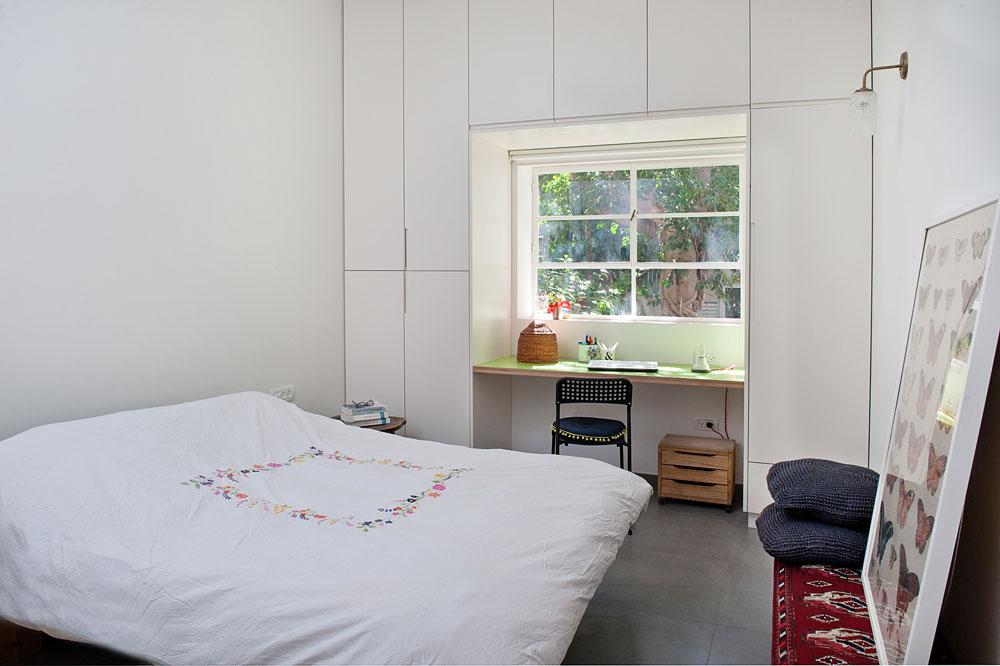 גם בחדר ההורים ארון גדול, ש''עוטף'' חלון ועמדת כתיבה, עשויה מפלטת פורמייקה פשוטה (צילום: גלית דויטש)