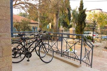 חצר ירושלמית עם אופניים. ''ארקדיה במושבה'' (צילום: דויד רוס)