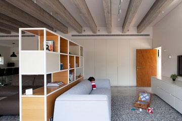 פינת המשפחה מופרדת מהסלון באמצעות ספרייה (צילום: עמית גרון)