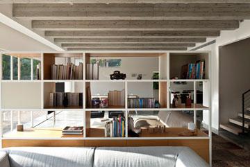 הספרייה עשויה ברזל ועץ אלון, מכילה משחקים וספרים ומסתירה את מערכות המדיה. מימין המדרגות לקומת המגורים (צילום: עמית גרון)