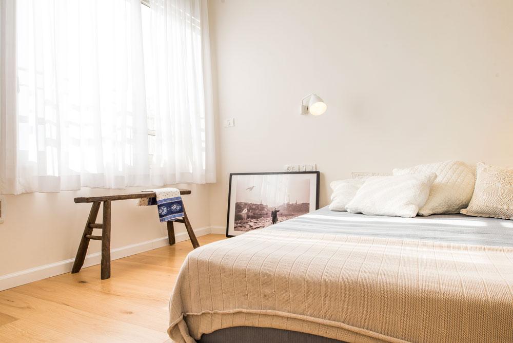 חדר ההורים עוצב בצבעים בהירים ורוהט בצמצום: מזרן עבה משמש כמיטה, ולצדו ספק שרפרף ספק ספסל עץ ישן  (צילום: גל דרן)