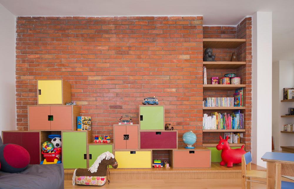 קיר הלבנים האדום היה בדירה לפני השיפוץ והוחלט להשאירו ולהשתמש בו כדי להגדיר את אזור המשחקים. למרגלותיו נבנתה במת עץ, ועליה תוכננו מדפים וקופסאות עץ עם דלתות פורמייקה צבעוניות (צילום: גל דרן)