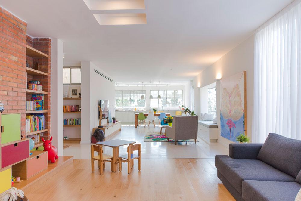 המרחב המשותף תוכנן לאורך כל הדירה, מהמטבח שבעומק התמונה ועד לאזור המשחקים. משמאל נראית הספרייה שבמבואת הכניסה (צילום: גל דרן)