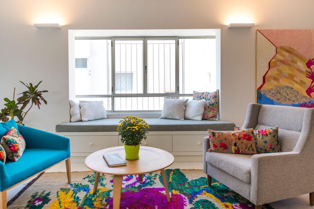 פינת הישיבה במרכז החלל מוסיפה צבע, עם שטיח ססגוני וספסל ישיבה בנוי, שתחתיו שלוש מגירות אחסון (צילום: גל דרן)