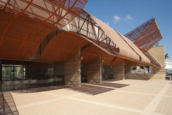 חזיתו השקופה של המועדון. אף שהמבנים שונים בעיצובם, נשמרת האחידות בשימוש באבן כורכר מקומית שאותה רואים בנדבכים הנמוכים של כל מבנה (צילום: טל ניסים )