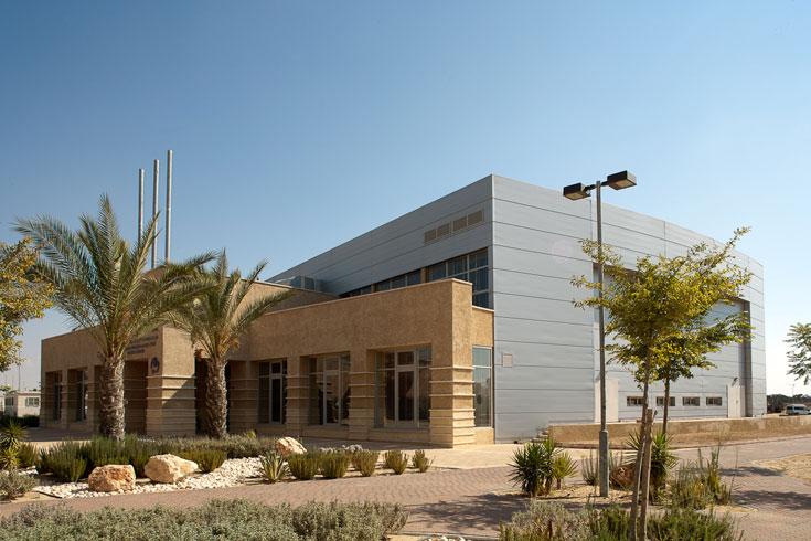 מרכז הספורט של מחנה רעים. השימוש באבן ובטיח המבוסס על כורכר גרוס מעניק תחושה שהמבנים צומחים מתוך הקרקע החולית (צילום: טל ניסים )