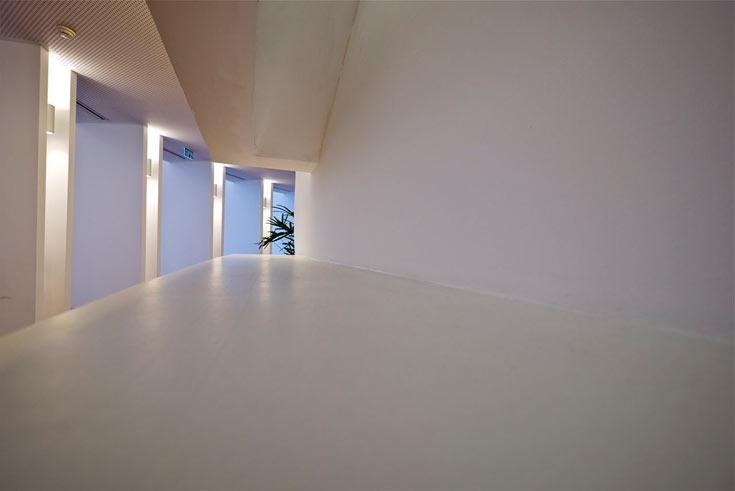 מעבר בתוך הבימה. ''התאורה המלאכותית עוקבת אחר קווי הארכיטקטורה הישנים והחדשים, ומדגישה את העומק והתלת-ממד של המבנה'' (צילום: איתי סיקולסקי)