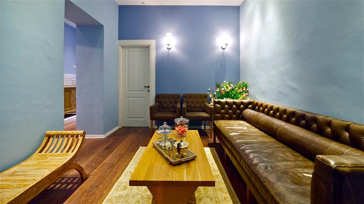 חלל המבואה. ספה בסגנון קפיטונאז', כורסאות בד, שולחן וספסל מעץ, שמשלימים את פרקט האגוז שמכסה את הרצפות הפשוטות (צילום: איתי סיקולסקי)