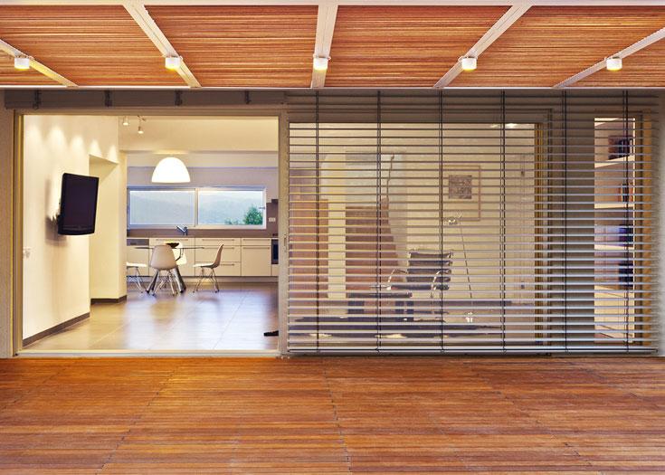 מבט מהגינה לתוך הסלון. הפתחים בקירות הורחבו בכל הבית. הקיר שעליו תלוי מסך הטלוויזיה הוא הקיר המחבר בין שני הבתים הישנים (מנורות: ''קמחי תאורה''. נגרייה: ''ניקולא'', נצרת עלית. ציורים: ברכה ביינ'ונידה גיא) (צילום: טל קרת)