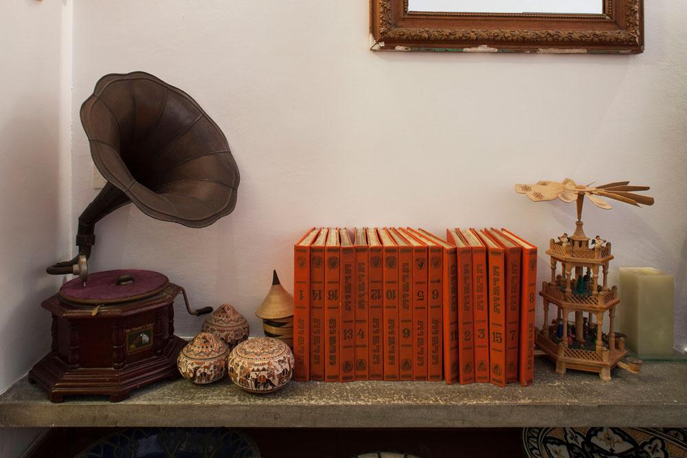על הקיר מראה ישנה מפריז, על המדף גרמופון, עוד פריטים מטיולים בעולם ואנציקלופדיית ''תרבות'': ''אז זה נראה קצת ערבובייה. אני לא אוהב דירות שנראות כמו מוזיאון. זו דירה שחיים בה, ואנחנו שמים את מה שאנחנו צריכים ואוהבים'' (צילום: אביעד בר נס)