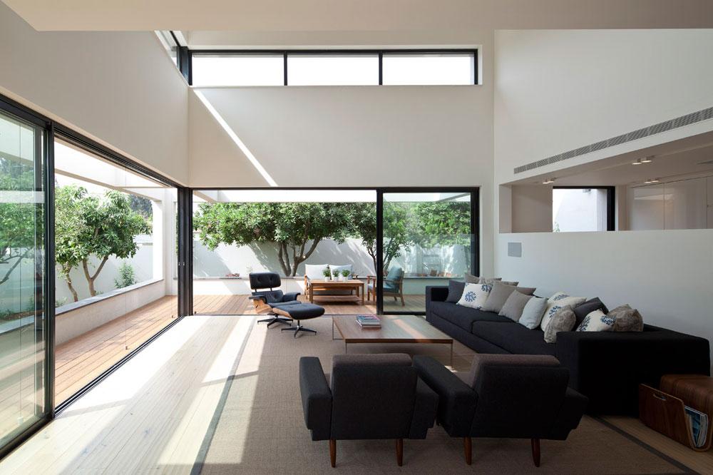 רהיטים קלאסיים וצבעים מונוכרומטיים. אור נוסף חודר דרך חלונות הסרט הגבוהים, המקשרים בין שני מפלסי הבית (צילום: עמית גרון)