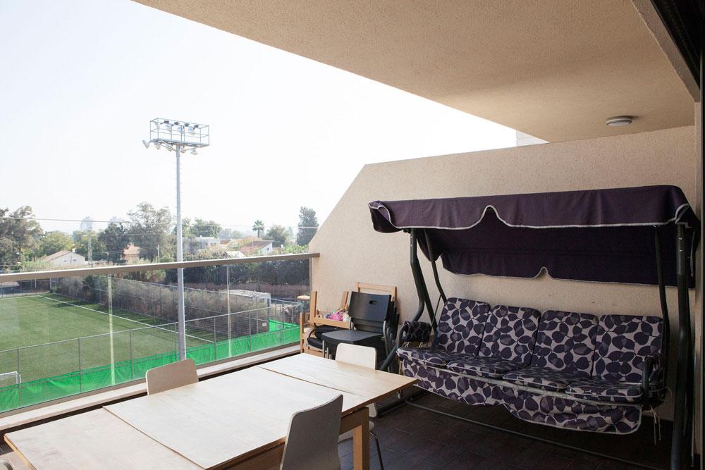הנדנדה במרפסת מרגיעה את טליה הקטנה ומאפשרת להשקיף על המשחקים במגרש הכדורגל ממול (צילום: אביעד בר נס)