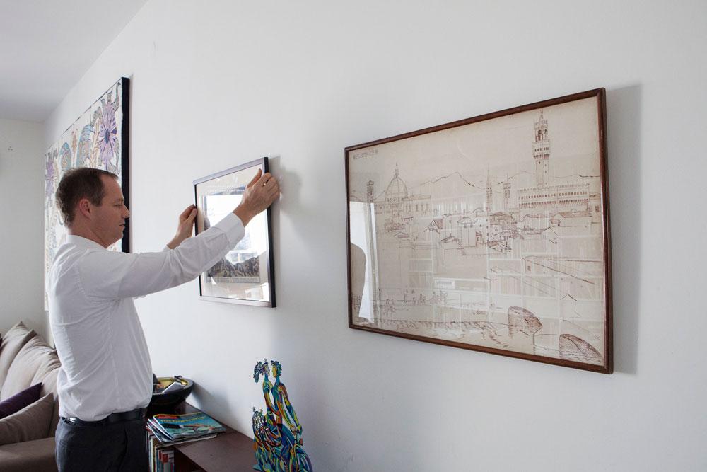 תמונות עם סיפור: מימין ציור נוף שציירה סבתו של פלסנר מחלון ביתה בפירנצה, ומשמאל הדפס מהמאה ה-18 שקיבל מנועם ברדין, חבר ילדות קרוב והיום מנכ''ל waze. ההדפס מתאר את הקרב בין יהושע לחמשת המלכים, ''הדפס שממחיש שאי אפשר לסמוך על הנס. בקרב הזה אלוהים חולל נס, אבל היה צריך גם להילחם'', מסביר פלסנר, שעמד בראש הוועדה ''לקידום השיוויון בנטל'' (צילום: אביעד בר נס)