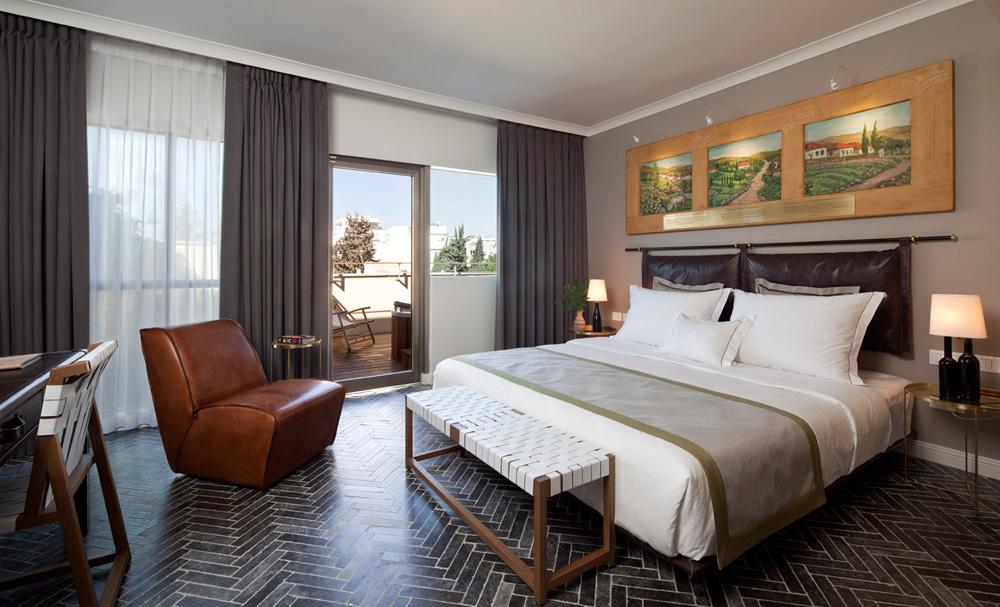 בכל אחד מהחדרים תלויות מעל המיטה שלוש תמונות שמן שמתארות סצינות ממושבות הברון. לצדי המיטה שולחנות מזרחיים, והמנורות מחווה לתעשיית היין של הברון (צילום: עמית גרון)