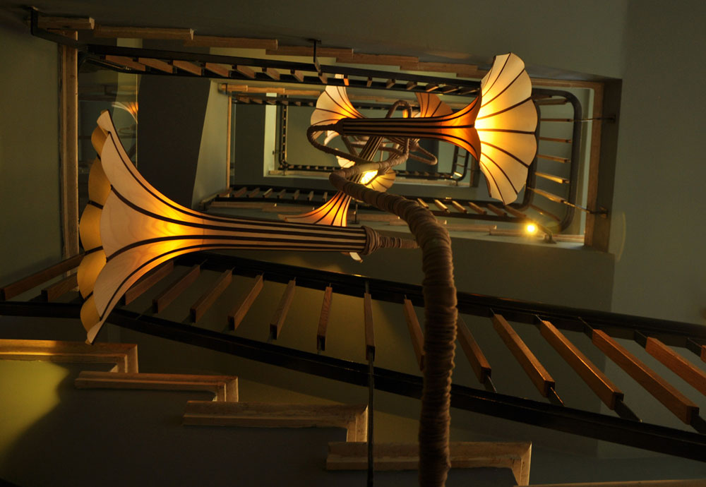 המנורה/מובייל של אביעד פטל. עוצבה בהשראת צמח מטפס: ה''גבעול'' עשוי מתכת מחופה בבד עם קפלים אקראיים, והאהילים של תשעת ה''פרחים'' שלו עשויים חלקי פורניר דק, תפורים במכונת תפירה תעשייתית. כל  פרח פונה לכיוון אחר ומאיר חלק אחר של גרם המדרגות (צילום: עדי ליקוורניק)