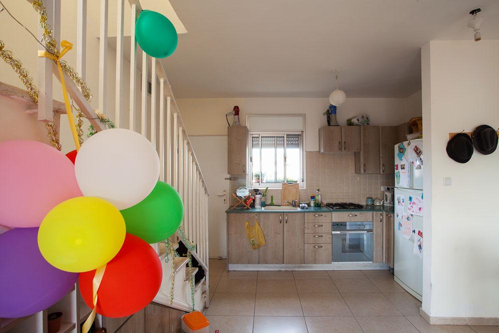 על ארונות המטבח מונחים מגאפונים, מוכנים לשימוש. הבלונים הם מיום ההולדת שחגגו לבתו בת השלוש של אחד השותפים (צילום: טל ניסים)