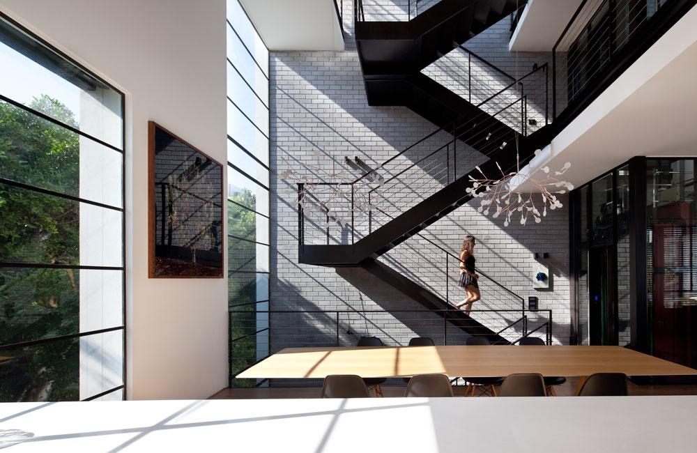 מבט מכיוון המטבח אל פינת האוכל, גרם המדרגות והמעלית. מימין למעלה נראית הקומה הרביעית שפונה אל פנים הבית ולא אל הרחוב, ובה חדר עבודה גדול (צילום: עמית גרון)