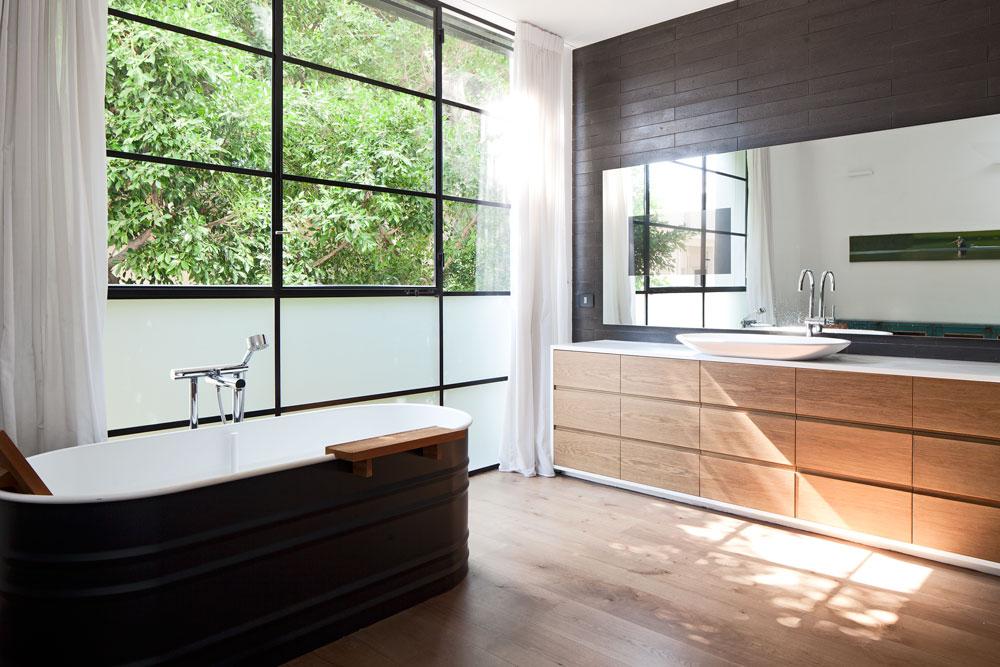 חדר הרחצה בקומת ההורים גדול ומואר. האמבט ניצב ליד חלון שמשקיף לנוף ירוק וגם כאן הצבעים השולטים הם עץ, לבן ושחור (צילום: עמית גרון)
