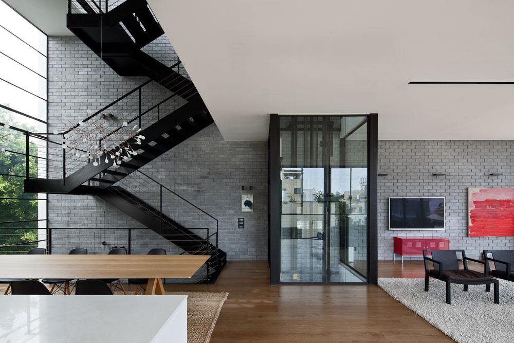 לגובה הבית נמתח חלל פתוח שבו גרם מדרגות מפלדה שחורה, שחלקיו הובאו לאתר הבנייה מוכנים ורותכו במקום. המדרגות נראות כאילו הן תלויות באוויר, ללא תמיכת קיר אריחי הסיליקט שלצידן (צילום: עמית גרון)