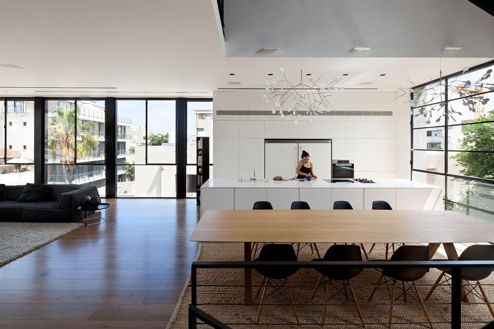 הקומה השלישית היא חלל גדול ופתוח עם אפיל ''לופטי'', שבו סלון, פינת אוכל מרווחת ומטבח. המנורה שמעל שולחן האוכל היא של המותג ההולנדי moooi (צילום: עמית גרון)