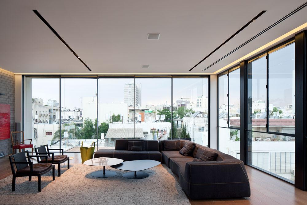 הסלון. רצפת כל הקומות חופתה פרקט, החלונות ממוסגרים בפרופיל ברזל שחור והרהיטים הם של מותגים כמו ''קפליני'', ''ויטרה'' ו''B&B ITALIA'' (צילום: עמית גרון)