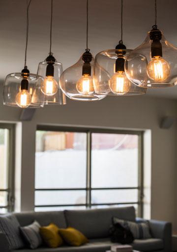 חמש מנורות זכוכית שונות מעל שולחן האוכל (צילום: איתי בנית)
